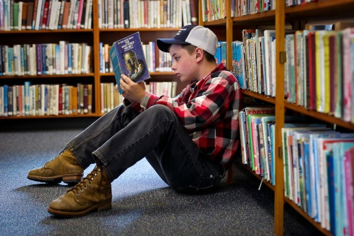 Darin Jenneskens, 11, reads through the first few pages of a Hardy Boys mystery while relaxing against an aisle of books at the new Plummer Public Library. The new facility opened to the public Monday.