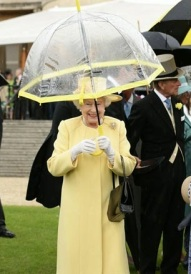 Britain's Queen Elizabeth II holds her umbrella as she meets guests as she hosts a Garden Party at Buckingham Palace in central London on June 3, 2014. AFP PHOTO / POOL / YUI MOK